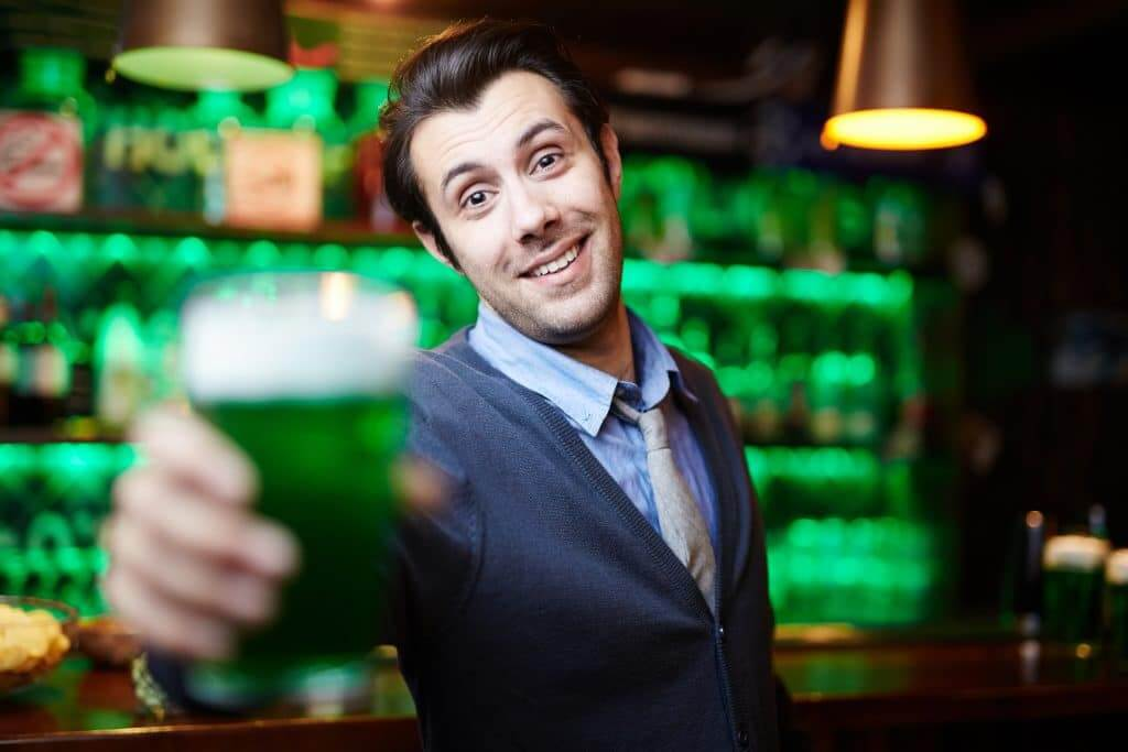 Smiling man with glass of irish beer toasting with you in pub